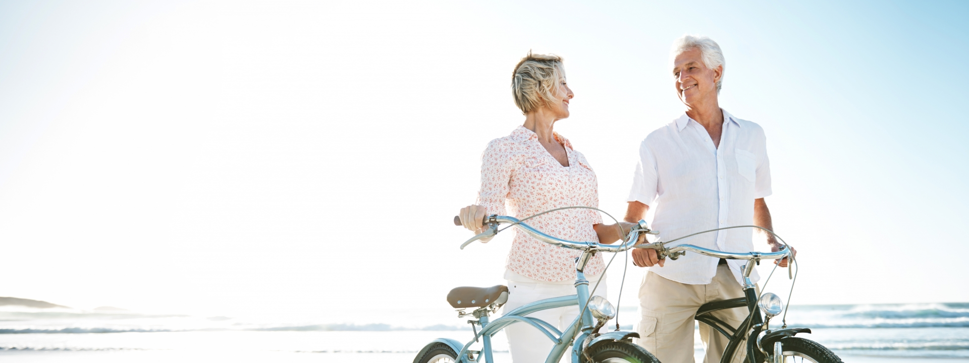Two active seniors with their bicycles on the beach