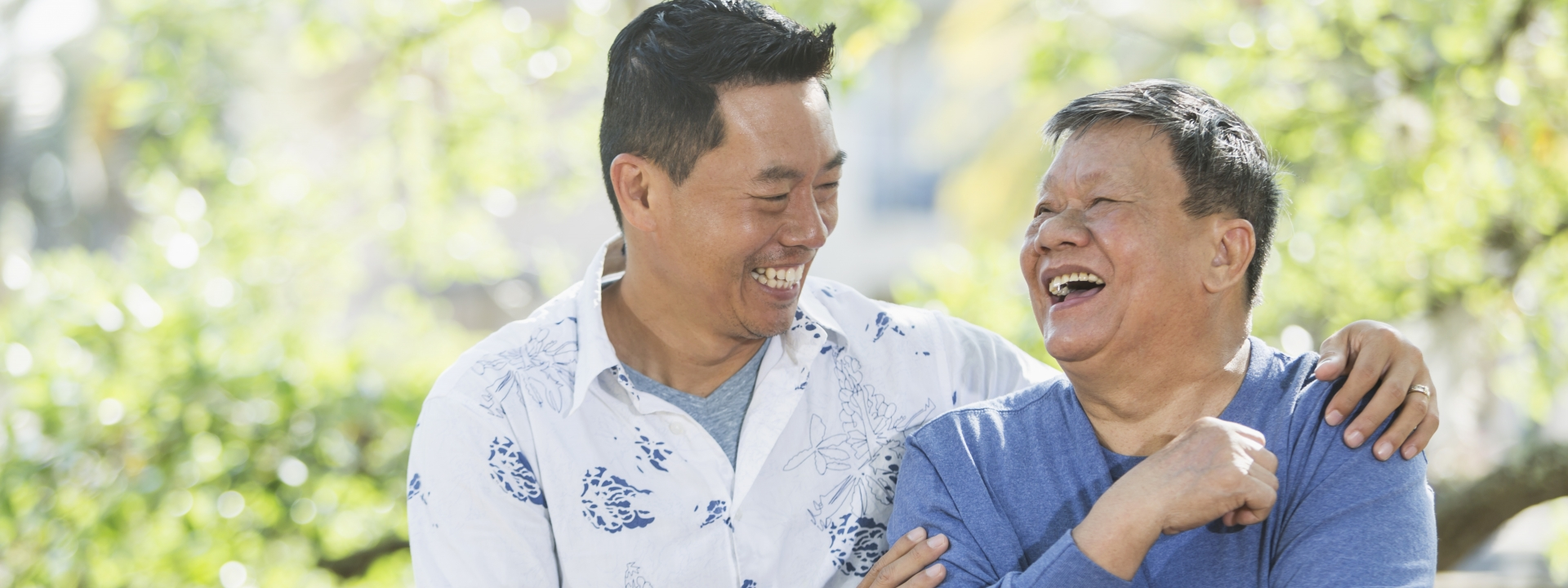 Senior Asian man and adult son laughing together